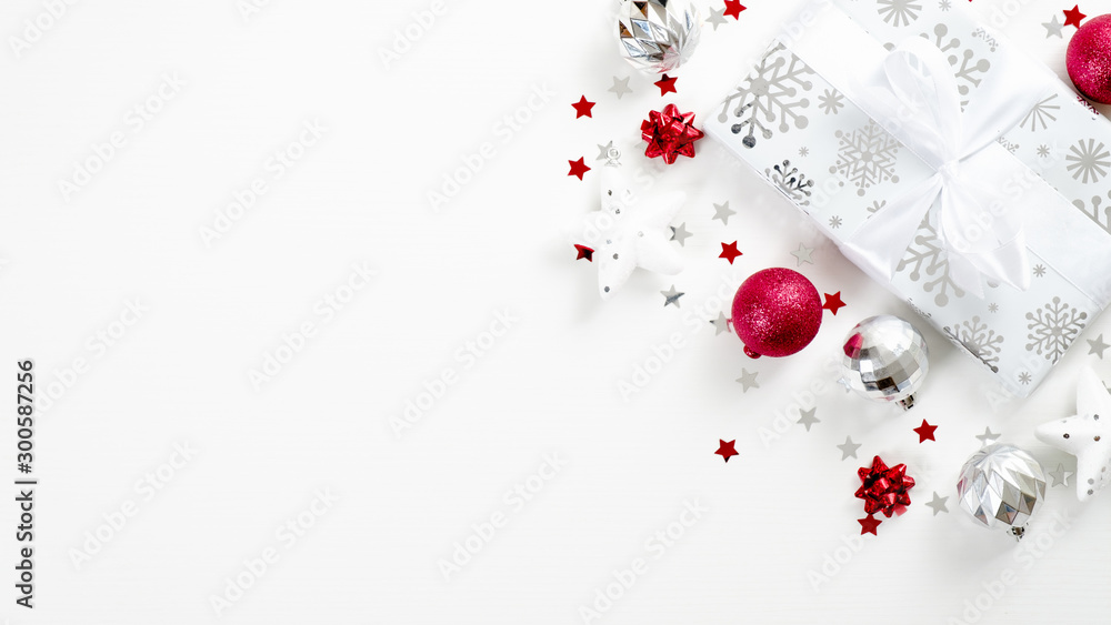 Fototapeta Top view Christmas present and silver and red decor elements on white background. Flat lay gift box with ribbon bow, balls, stars, confetti. Christmas, winter holiday, New Year concept.