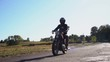 Biker rides on his motorcycle on the asphalt in slow motion.middle plan.Biker rides on his old motorcycle