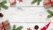 Christmas Background With Decorations On White Wooden Surface. Copy Space In The Middle. Gifts, Fir Branches, Cones And Candle On Desk. Top View, Flat Lay Composition.