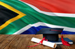 canvas print picture - South Africa education concept. Graduation cap and diploma on wooden table, national flag background. Succesful student.
