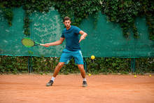 Skilled And Agile Tennis Player Having A Practice At Outdoor Court.