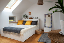 Interior Of Modern Bedroom In Bright Apartment In The Attic. Room In A Hotel With Double Bed With White Furniture And Grey Pillows. Scandinavian Style Indoors.