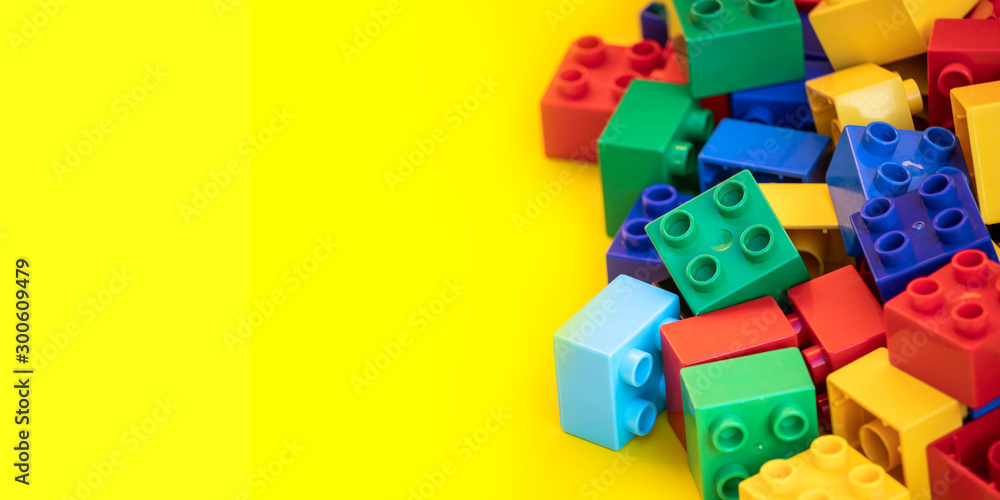 Fototapety, obrazy: Colorful plastic building blocks toy bricks with place for you text and content.