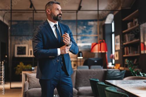 Cuadros en Lienzo Stylish bearded man in a suit standing in modern office