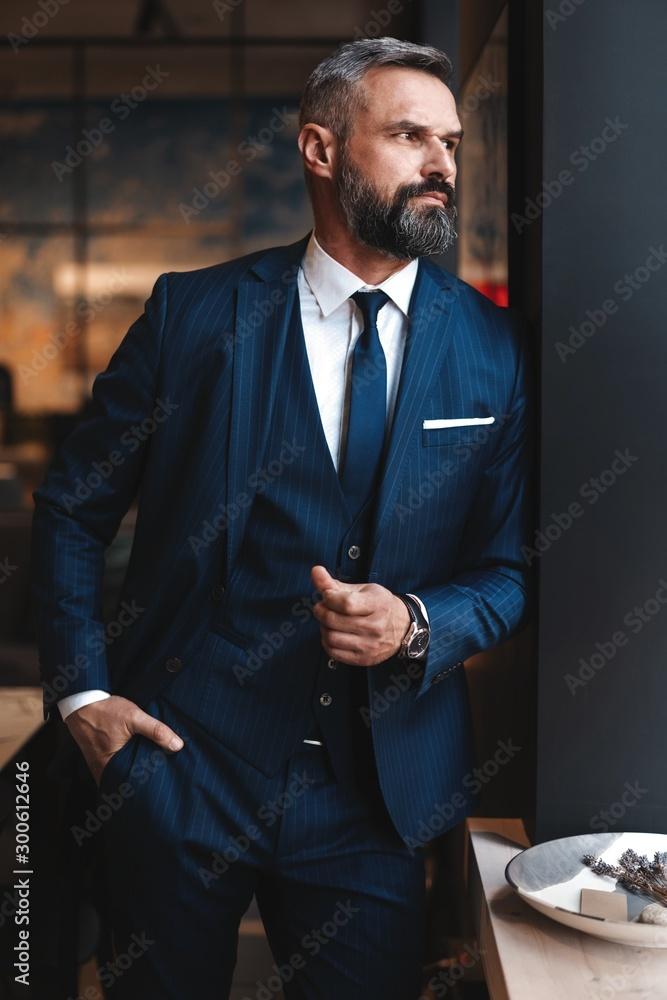 Fototapeta Stylish bearded man in a suit standing in modern office