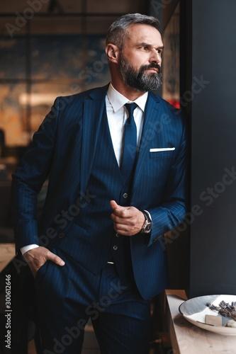 Obraz Stylish bearded man in a suit standing in modern office - fototapety do salonu
