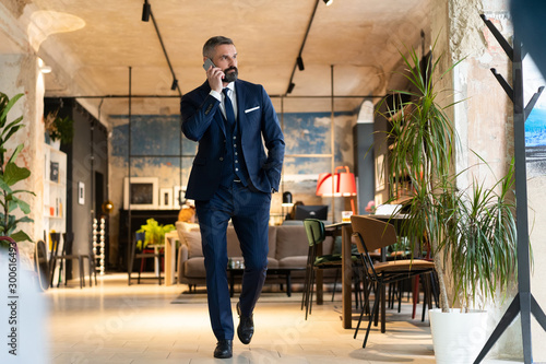 Fotomural  Stylish bearded man in a suit standing in modern office