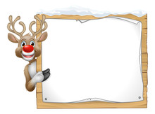 Reindeer Christmas Cartoon Character Peeking Around A Wooden Sign And Pointing At It