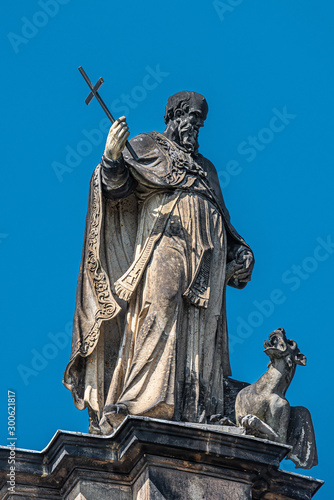 Fotografie, Tablou Very old roof statute of high ranked priest with a cross and a dragon in histori