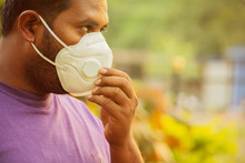 Asian Man Wearing The Face Mask Due To Air Pollution  Or Covid-19 Outbreak - Young Adult On Park With Pollution Mask - Person Protecting From Air Contamination And Coronavirus By Wearing Mask.