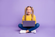 canvas print picture - Full size photo of amazed child sit folded crossed legs work computer get social media notification scream wow omg wear yellow pullover sneakers isolated over purple color background