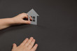 Close up horizontal image of child's hands holding white paper house on gray background. Family home and real estate concept. Flat lay, copy space