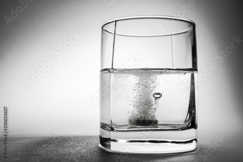 Photo Effervescent aspirin tablet dropping to glass of water