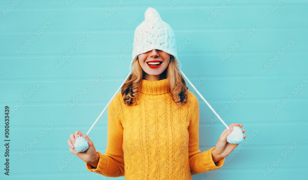 Fototapety, obrazy: Winter portrait happy smiling young woman having fun pulls a hat over her eyes wearing yellow knitted sweater and white hat with pom pom on blue wall background