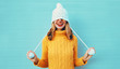 Winter portrait happy smiling young woman having fun pulls a hat over her eyes wearing yellow knitted sweater and white hat with pom pom on blue wall background