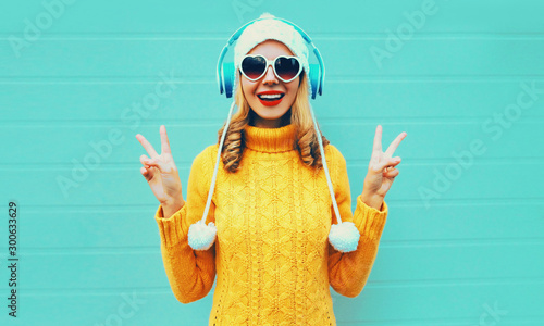 Autocollant pour porte Magasin de musique Winter portrait happy smiling young woman in wireless headphones listening to music wearing yellow knitted sweater and white hat with pom pom, heart shaped sunglasses on blue wall background