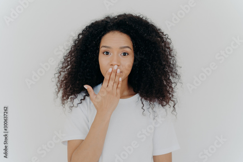 Fotografie, Tablou  Headshot of impressed curly young woman covers mouth with palm, tries to be speechless, has curly hairstyle, manicure and minimal makeup, wears white t shirt, poses indoor