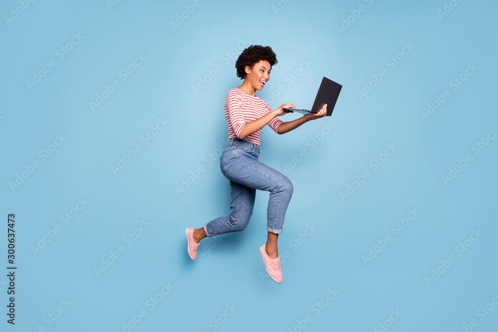 Fototapeta Full length body size side profile photo of pretty cheerful cute nice charming youngster typing before laptop wearing jeans denim striped shirt isolated pastel color blue background