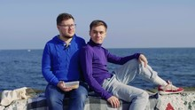 Two Gays Representing The LGBT Community, Sit And Hold A Box Of Butybrod On A Stone Pier And Bedding Against The Background Of The Sea And Look Past The Camera