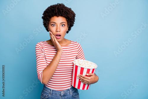 Fotografie, Obraz  Photo of frightened feared girlfriend with popcorn in striped shirt jeans denim