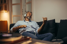 Mid Aged Man Relaxing In His Home Listening To A Music