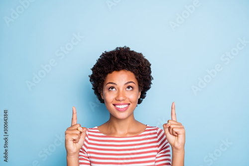 Photo of curly cheerful positive nice pretty girlfriend pointing up to show you necessary information to be posted above to follow smiling toothily in striped shirt isolated pastel blue color