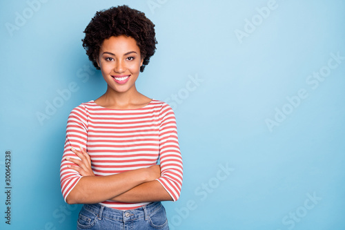 Obraz Photo of cheerful toothy beaming positive girlfriend with arms crossed near empty space wearing jeans denim isolated over blue pastel color background - fototapety do salonu