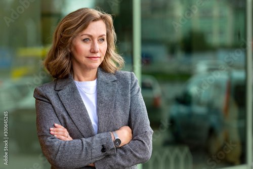 plakat Portrait of a pretty mature business woman 55 years old, outdoors in the city.