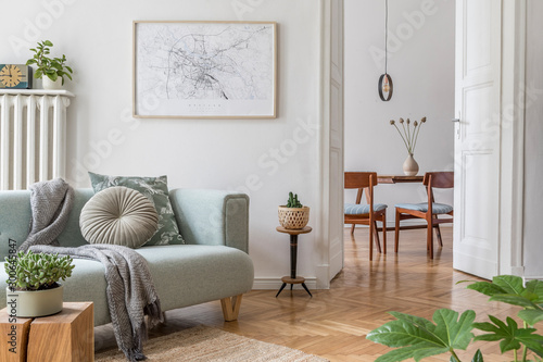 Obraz Stylish scandinavian living room and dining room with design mint sofa, mock up poster map, plants and elegant personal accessories. Modern home decor. Open space. Template. Ready to use.  - fototapety do salonu