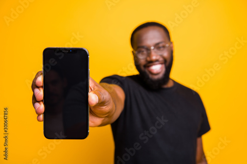 Portrait of positive afro american guy hold smartphone show modern technology gadget advertise promotion wear casual style outfit isolated over yellow color background