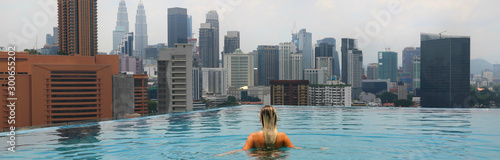 Photo  Young happy girl swimming alone in the infinity pool on rooftop in Kuala Lumpur in Malaysia