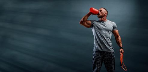 Prehrambeni dodatak. Mišićavi muškarci piju proteine, energetski napitak nakon treninga