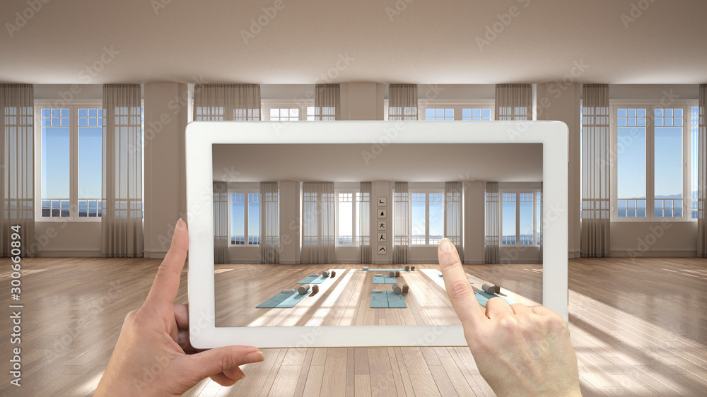 Fototapety, obrazy: Augmented reality concept. Hand holding tablet with AR application used to simulate furniture and design products in empty interior, parquet floor, empty yoga studio with accessories