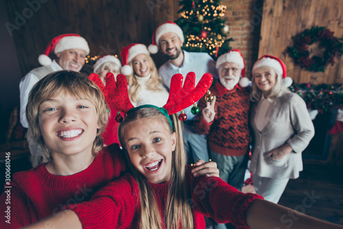 Self photo of large family meeting together with couple of brother sister taking selfie on background of their relatives parents grandparents and christmas tree in lights