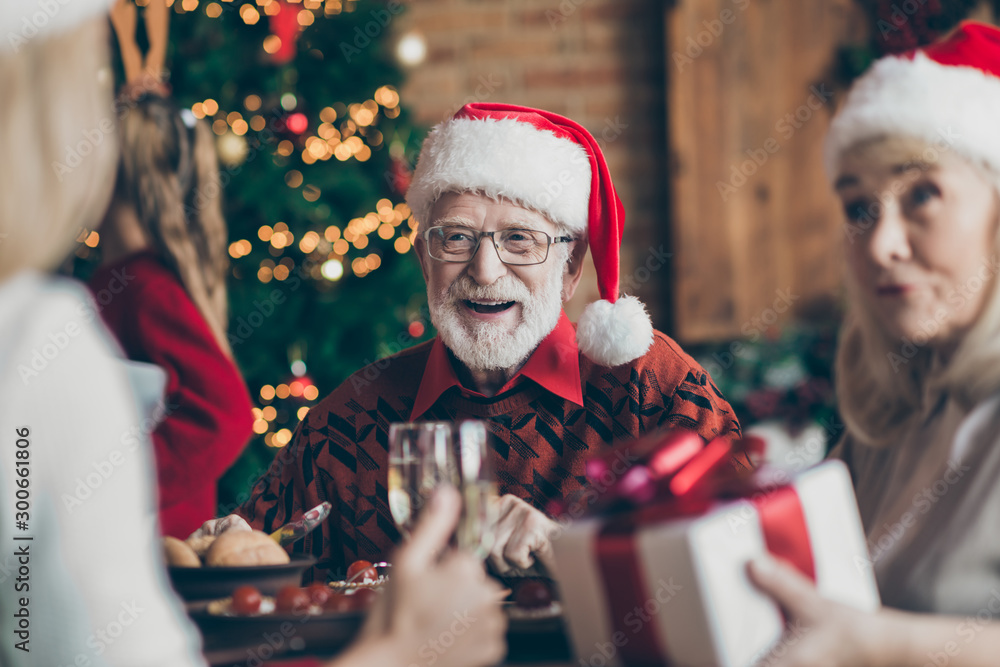 Fototapeta Phot of grandfather positive cheerful smiling in eye glasses spectacles wearing santa hat headwear feeling festive mood in conversation with guests