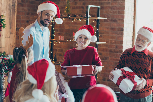 Photo of cheerful positive cute nice large family wearing cap headwear holding gift boxes with granddad in glasses couple mother father rejoice