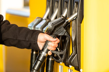 Hand With Fuel Nozzle At A Gas...