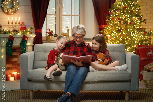 Grandmother reading  to granddaughters near Christmas tree. Canvas Print