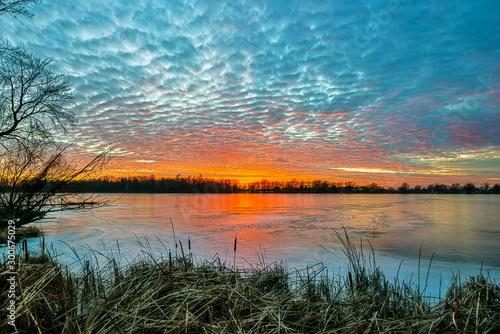 Foto auf Leinwand Khaki Sunset on Frozen Lake with Clouds