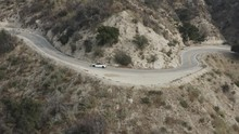 Aerial Shot Of A Fast, White Car Taking A Sharp Turn On The Windy Interstate Roads Found In The Desert Hills Of California.