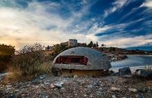 Mililitary Concrete Bunker Or Pillbox In The Southern Albania Built During The Communist Government Of Enver Hoxha. Big Bunker On Background Of Lekuresi Castle, Saranda, Albania On Sunset.