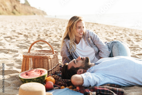 Lovely young couple having a picnic at the beach Fototapeta