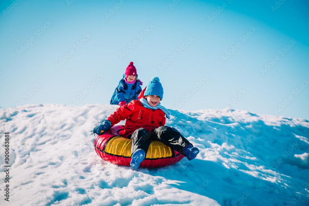 Fototapeta happy cute boy and girl slide in winter snow