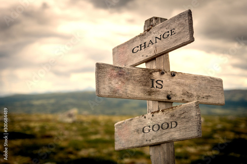 Foto Change is good quote on wooden signpost in nature with moody background