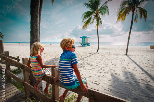 boy and girl looking at tropical beach with palms, family on vacation in Florida Wallpaper Mural