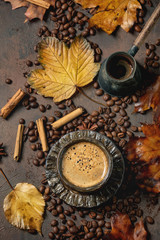Black coffee espresso with foam in black ceramic cup, with saucer, cezve coffee pot, autumn leaves, spices and roasted beans above over brown texture background. Flat lay