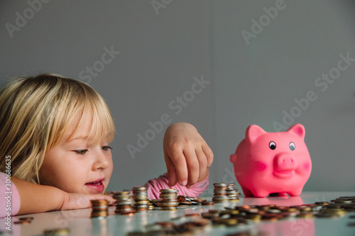 child saving money, cute girl put coins into piggy bank