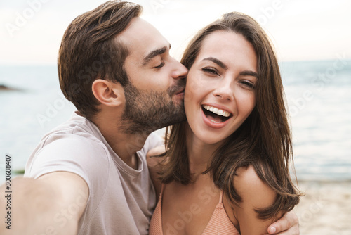 Image of young happy man kissing and hugging woman while taking selfie Tableau sur Toile