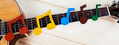 Obraz Music and guitar panorama - musical notes on guitar fretboard for music concepts, playing guitar and learning a musical instrument. Fun design for inspiration. - fototapety do salonu