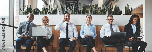 Photo  Diverse businesspeople smiling while waiting together in an offi